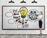 Blondes Mädchen nahe whiteboard mit Geschäftsikonen Lizenzfreie Stockfotos