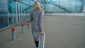 Blondes Mädchen rollt einen Koffer nahe dem Flughafenabfertigungsgebäude - Ansicht von der Rückseite stock video