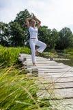 blondes Mädchen 20s, das Balance auf Brücke von Teich ausübt Lizenzfreies Stockfoto