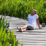 blondes Mädchen 20s, das in der Sonne draußen sich entspannt liegt Stockbild