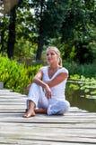 blondes Mädchen 20s, das in der Sonne draußen sich entspannt träumt lizenzfreie stockbilder
