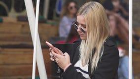 Blondes Mädchen schwingt an der Straße stock footage