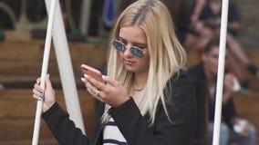 Blondes Mädchen schwingt an der Straße stock video footage