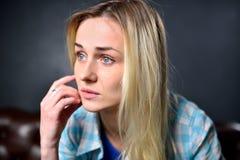 Blondes Mädchen sitzt auf einem braunen Sofa im Hintergrund von einem GR Lizenzfreies Stockbild