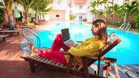 Blondes Mädchen sitzt auf Klappstuhl-Arbeiten über Laptop durch Pool stock footage