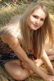 Blondes Mädchen sitzt auf Weizen Stockbild