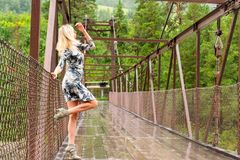 Blondes Mädchen steht auf einer Brücke, die aus dem Metall und Holz konstruiert wird stockbild