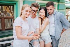 Blondes Mädchen steht mit ihren Freunden und hält Telefon in der Hand Alle betrachten es und das Lächeln Blond Stockbild