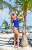 Blondes Mädchen am Strand wirft nahe Palme auf Lizenzfreies Stockbild