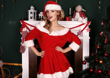 Blondes Mädchen trägt Sankt-Kostüm und wirft neben Weihnachtsbaum und Kamin auf Lizenzfreies Stockbild