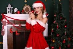 Blondes Mädchen trägt Sankt-Kostüm und wirft neben Weihnachtsbaum und Kamin auf Stockfoto