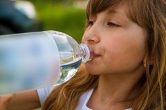 Blondes Mädchen 7-9 trinkend von der Wasserflasche, Seitenansicht stockfoto