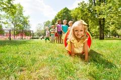 Blondes Mädchen und ihre Freunde spielen im Rohr auf Rasen Stockbild