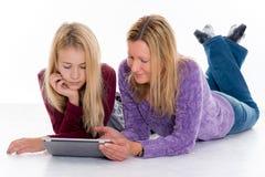 Blondes Mädchen und ihre Mutter, die Tablet-PC verwendet Stockfotos