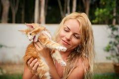 Blondes Mädchen und rotes Kätzchen nahe Haus Stockbilder