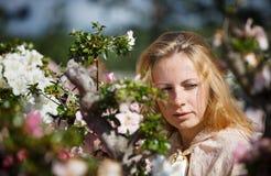 Blondes Mädchen unter den Blumen Stockfoto