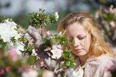 Blondes Mädchen unter den Blumen Lizenzfreie Stockbilder