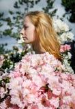 Blondes Mädchen unter den Blumen Stockfotografie