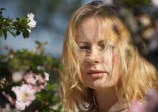 Blondes Mädchen unter den Blumen Stockfotos