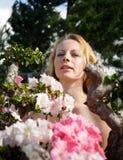 Blondes Mädchen unter den Blumen Stockbilder