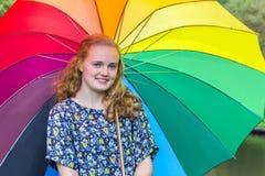 Blondes Mädchen unter Regenschirm mit verschiedenen Farben Lizenzfreie Stockfotografie