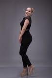 Blondes Mädchen verwirrt, angekleidet im Schwarzen lizenzfreie stockfotos
