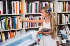 Blondes Mädchen wählt ein Buch Lizenzfreie Stockbilder