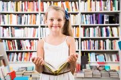 Blondes Mädchen wählt ein Buch in der Bibliothek Stockfotos