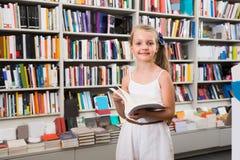 Blondes Mädchen wählt ein Buch in der Bibliothek Stockfoto