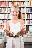 Blondes Mädchen wählt ein Buch in der Bibliothek Lizenzfreies Stockbild