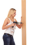 Blondes Mädchen, welches die Wand bohrt Stockfotografie