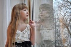 Blondes Mädchen, welches heraus das Fenster schaut lizenzfreie stockfotografie