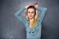 Blondes Mädchen zeigt lustiges Gesicht Lizenzfreie Stockfotografie