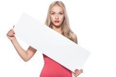 Blondes Mädchen zeigt Plakat. Lizenzfreie Stockfotos