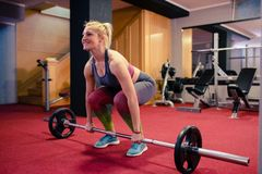 Blondes Mädchengewichtheben an der Turnhalle Lizenzfreies Stockfoto