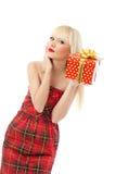 Blondes Mädchenholding-Weihnachtsgeschenk im roten Kleid Lizenzfreies Stockfoto