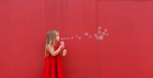 Blondes Mädchenkind im roten Kleid auf einem Hintergrund der Wand brennt Blasen durch Lizenzfreie Stockfotos
