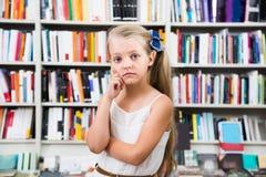 Blondes Mädchenkind verwirrte von der Auswahl von Büchern im Speicher Lizenzfreie Stockfotos