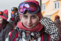 Blondes Mädchenporträt des Snowboard recht mit den grünen Augen, die purpurrote Maske und orange Hut mit dem Schal vorwärts schau Stockfoto