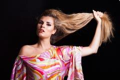 Blondes Mädchenschönheitsporträt halten ihr langes Haar in der Hand Stockfotos
