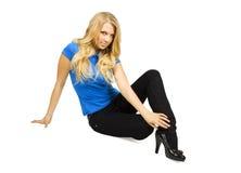 Blondes Mädchensitzen, Hand auf dem Fahrwerkbein, getrennt Stockfotografie