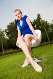 Blondes Mädchensitzen im Freien auf einem Schwenkerstuhl Stockfoto
