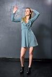 Blondes Mädchentanzen auf einem grauen Wandhintergrund Stockfoto