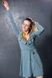 Blondes Mädchentanzen auf einem grauen Wandhintergrund Stockfotografie