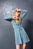 Blondes Mädchentanzen auf einem grauen Wandhintergrund Lizenzfreies Stockbild
