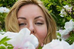 Blondes M?dchen auf einem Hintergrund von Blumen der Baum Pfingstrose stockfotografie