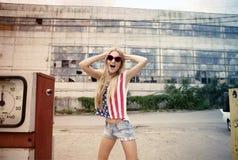 Blondes Mädchen auf geschädigter Tankstelle Lizenzfreies Stockfoto