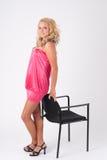 Blondes Mädchen, das auf einem Stuhl sich lehnt Lizenzfreies Stockfoto