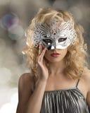 Blondes Mädchen mit silberner Schablone auf dem Gesicht Stockfoto