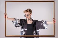Blondes Mode-Modell in der stilvollen Kleidung, die Holzrahmen hält Stockfotos